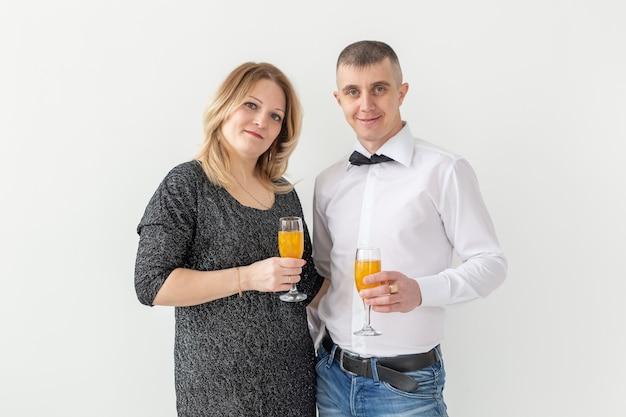 休日、クリスマス、バレンタインデー、新年のコンセプト-女性と男性は、白い背景の上にグラスでワインを祝い、保持します。