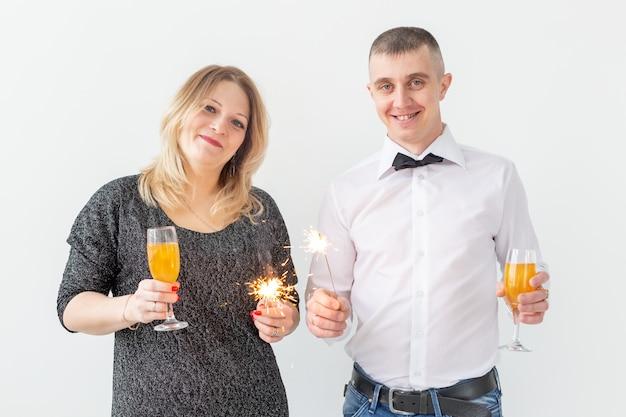 휴일, 크리스마스, 발렌타인 데이 및 새해 개념 - 여자와 남자는 흰색 배경 위에 와인을 잔에 들고 축하합니다.