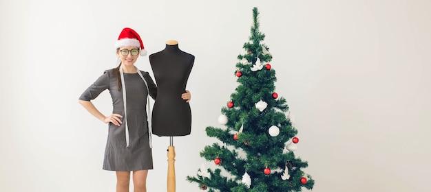 休日、服のデザイン、ギフトのコンセプト-クリスマスツリーの近くの女性の服のデザイナー、テーラリングスタジオのクリスマス。