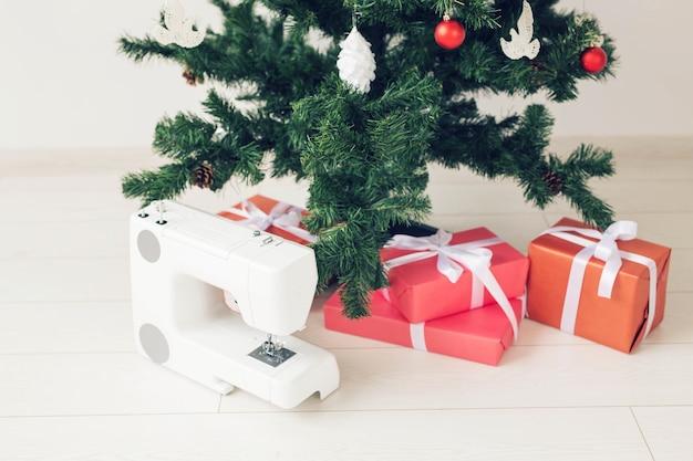 休日、服のデザイン、ギフトのコンセプト-クリスマスツリーの下のプレゼントとしてのミシン。