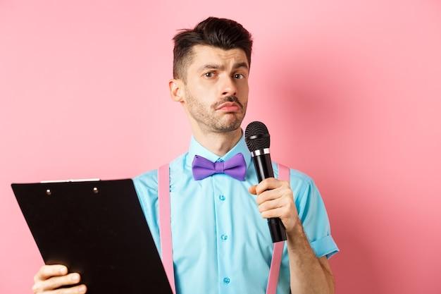 휴일 개념. 나비 넥타이가 연설을하고, 파티 이벤트에서 수행하고, 클립 보드와 마이크에 스크립트를 들고, 당신을 즐겁게하고, 분홍색 배경 위에 서있는 재미있는 남자.