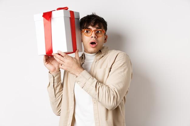 Концепция праздников. забавный молодой человек в очках трясет подарочной коробке, слушает то, что присутствует внутри, и задыхается от изумления, стоя на белой стене.