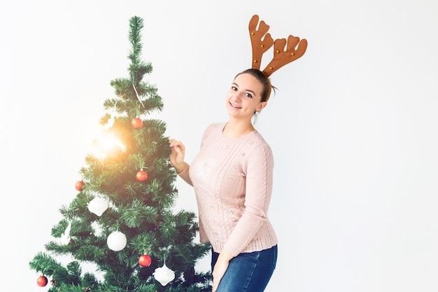 Концепция праздников - забавная молодая женщина украсила елку на белом фоне с копией пространства. ждет рождества.