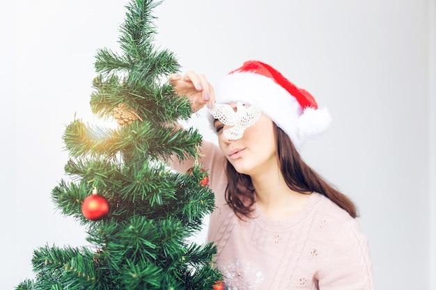 Концепция праздников - девушка в новогодней шапке украсила елку. ждет рождества.