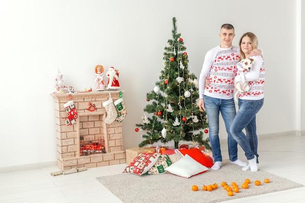 休日の概念-家のクリスマスツリーで幸せな家族の母の父と子。