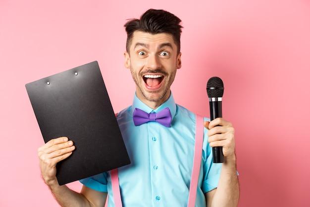 휴일 개념. 행복 한 젊은 남자 연예인 카메라에 웃 고, 클립 보드와 마이크를 들고, 파티 이벤트에 연설을 하 고, 분홍색 배경 위에 서.