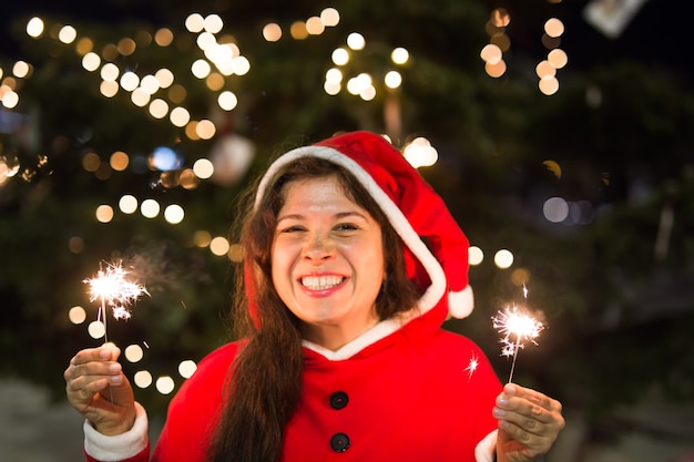 Holidays concept - smiling woman in christmas costume with lights or sparkles in her hands