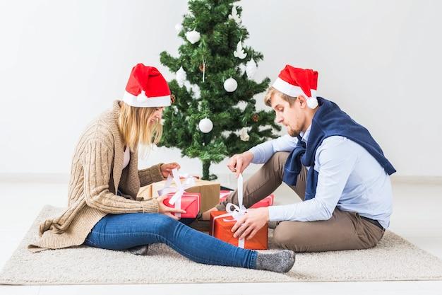 휴일 개념-거실에 앉아 크리스마스 선물을 여는 달콤한 커플