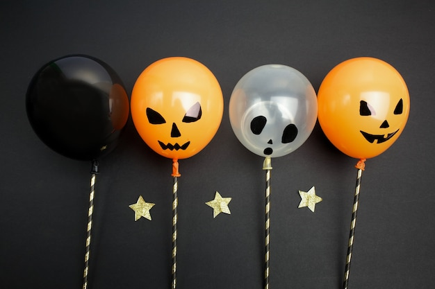 休日、装飾、パーティーのコンセプト-黒い背景の上のハロウィーンの気球上面図