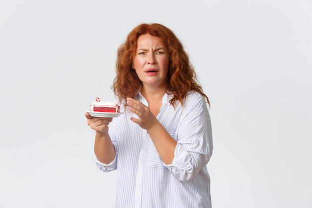 休日、感情、ライフスタイルのコンセプト。デザートのひどい味に不満を言ううんざりする顔をしかめる中年女性、ケーキや風味、白い壁からしがみつくのが嫌い