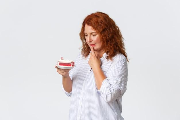 休日、感情、ライフスタイルのコンセプト。決断を下す赤い髪の優柔不断なかわいい中年女性。ケーキを食べたいがカロリーは気になり、デザートをじっと見ている。