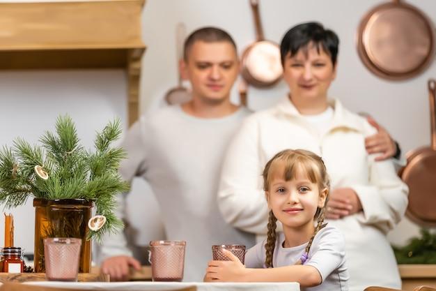 Праздники, семья и концепция празднования - счастливая мать, отец и маленькая дочь, имеющие рождественский ужин дома