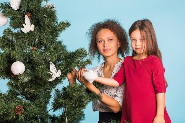 Праздники, семья и рождественская концепция - мать и дочь смешанной расы украшают елку