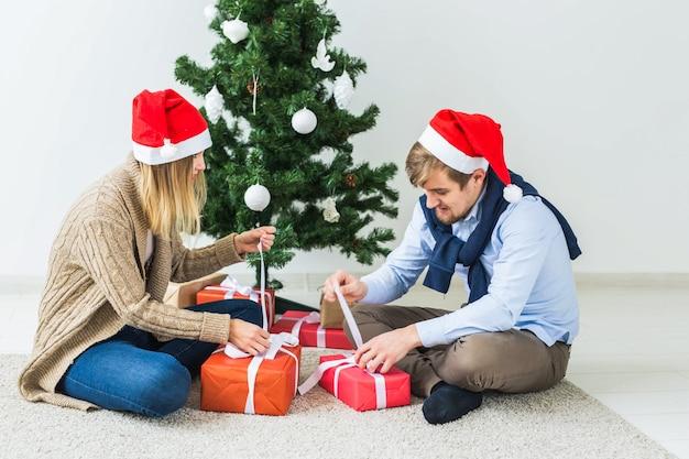 Праздники, семья и праздничная концепция - пара с рождественскими подарками дома.