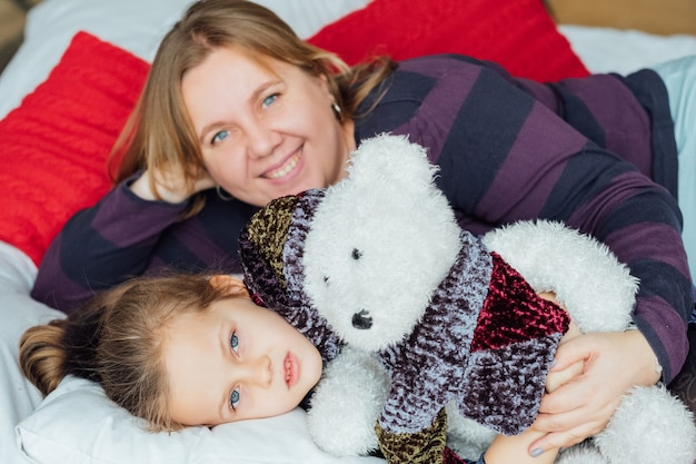 Holidays family leisure. loving mother hugging her cute little daughter. girl lying in bed with her teddy bear.