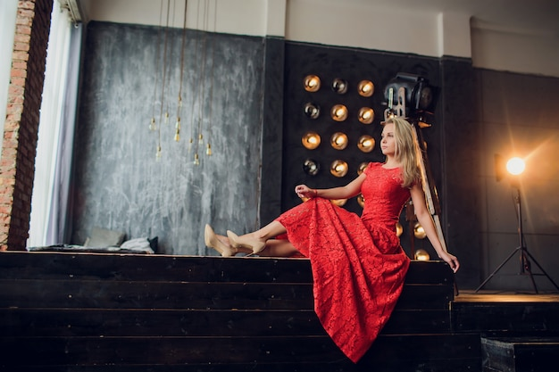 Holidays and fashion concept - beautiful sexy woman in red dress over lights background