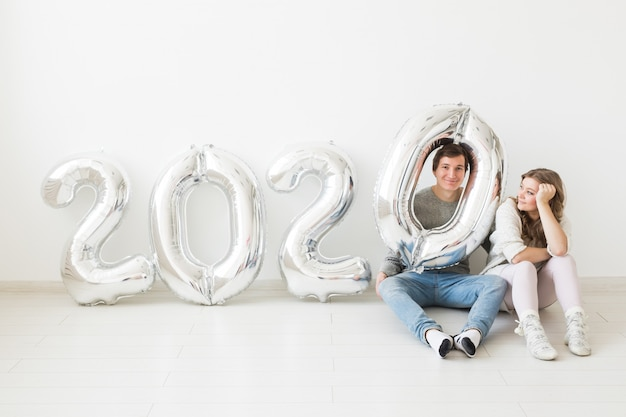 Концепция праздников, праздничных и партии - смешные пары сидя на поле около серебра раздувают 2020 воздушных шаров. новогодний праздник