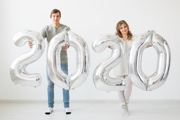 Концепция праздников, праздничных и партии - счастливая любящая пара держит серебряные воздушные шары 2020 года. новогодний праздник
