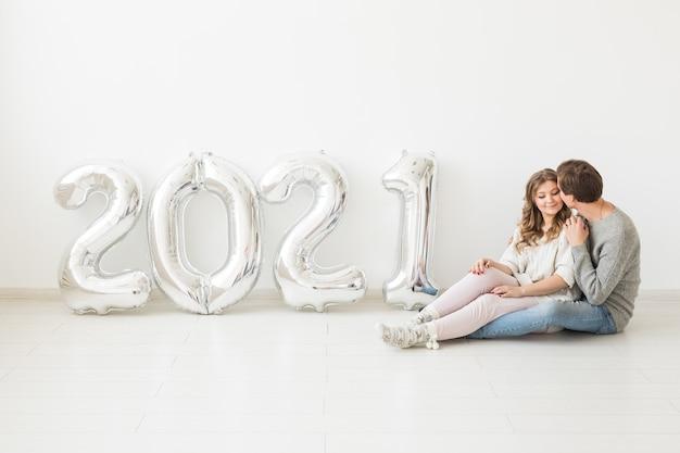 Концепция праздников, праздников и вечеринок - счастливая влюбленная пара держит серебряные воздушные шары 2021 года