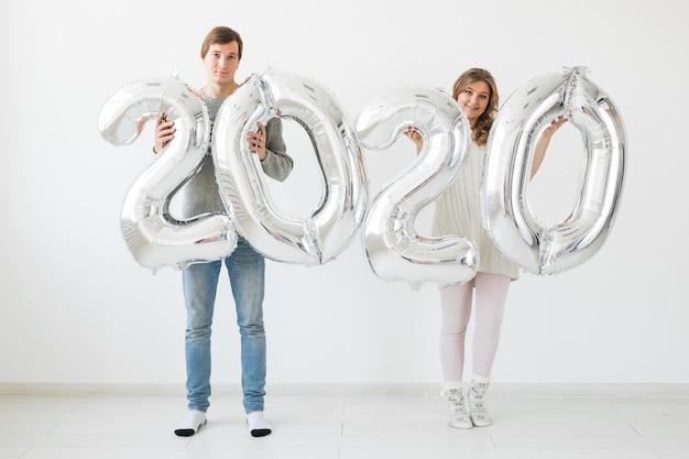 Концепция праздников, праздничных и партии - счастливая любящая смешная пара держит серебряные воздушные шары 2020 года. новогодний праздник