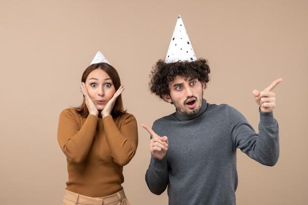 Праздники, праздничные и партийные концепции - счастливая любящая забавная пара, смотрящая в разные стороны