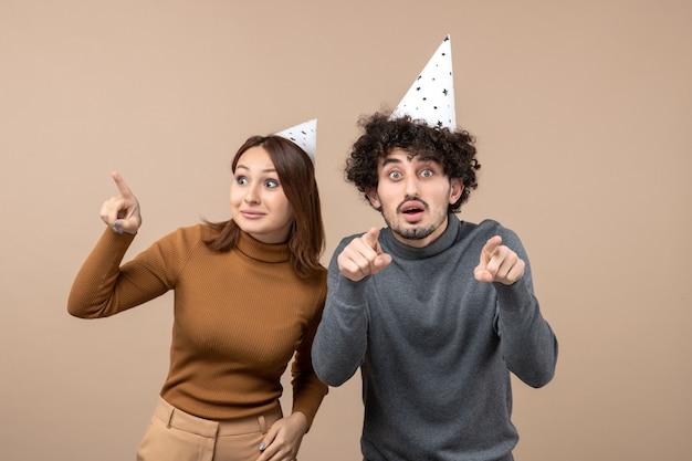 Праздники, праздничные и партийные концепции - счастливая любящая забавная пара, указывающая в разных направлениях