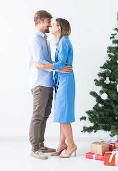 Holidays and festive concept - young happy couple near a christmas tree on white background.