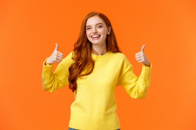 Holidays, gestures, people concept. cheerful cute redhead girl smiling and showing thumbs-up