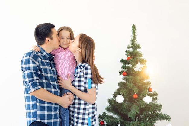 休日、ギフト、クリスマスツリーのコンセプト-クリスマスに一緒に幸せな時間を過ごす小さな家族。