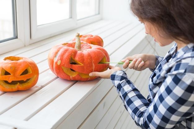 Праздники, хэллоуин, украшения и люди концепция - крупным планом женщина с тыквами готовится к хэллоуину