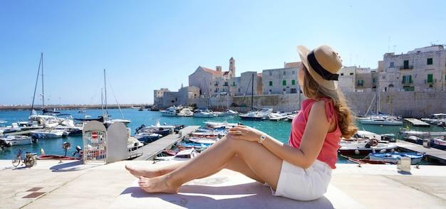イタリアの休日。プーリアのジョヴィナッツォ港の景色を楽しんで壁に座っている美しい少女の背面図。イタリアの夏休み。