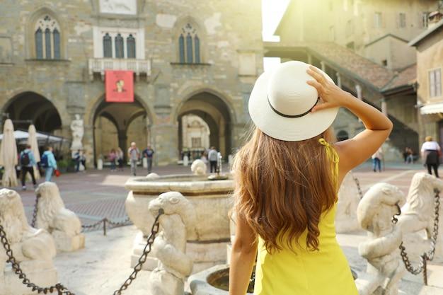 Отдых в италии. вид сзади молодой женщины, посещающей бергамо, типичный средневековый город региона ломбардия в италии.