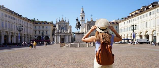 イタリアの休日。イタリア、トリノの街並みを楽しんでいるサンカルロ広場を歩いている旅行者の女の子のパノラマビュー。ヨーロッパを訪れる若い女性のバックパッカー。