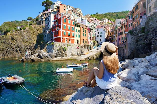 이탈리아의 휴일. 이탈리아 친퀘테레(cinque terre), 화려한 집들이 있는 리오마조레(riomaggiore) 마을의 도시 경관을 즐기는 돌 위에 앉아 있는 예쁜 젊은 여성.