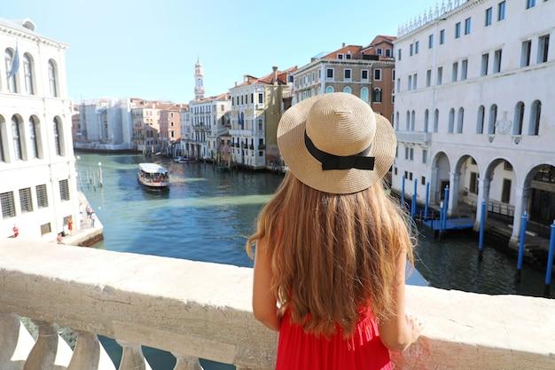 베니스의 휴일. 베니스, 이탈리아에서 리알토 다리에서 대운하의보기를 즐기는 빨간 드레스에 아름 다운 여자의 다시보기.