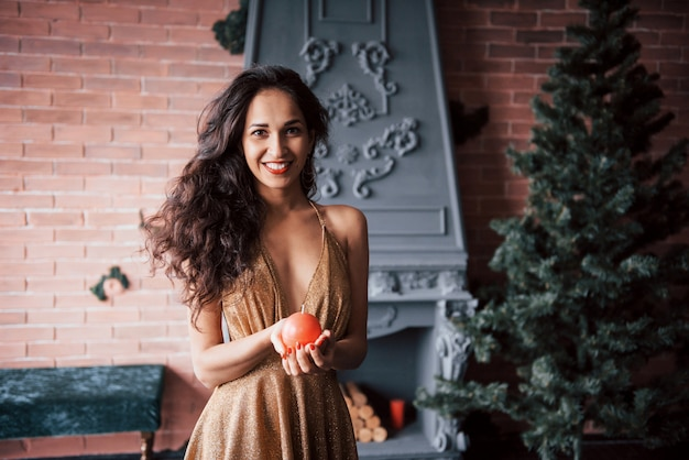 Holidays is coming. pretty brunette holding ball shaped candle while stands indoor near the fireplace and christmas tree