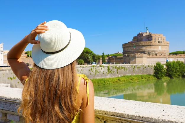 Holidays in italy. back view of beautiful tourist girl in rome, italy. attractive fashion woman looks at castel sant angelo castle on the bridge.