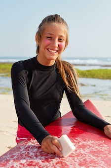 Holidays, lifestyle and summer time concept. glad young european female goes in for surfing, wears special suit
