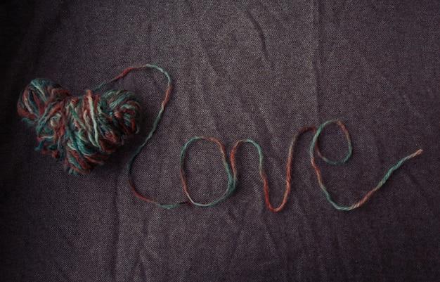 休日、愛、バレンタインデーのコンセプト-茶色の背景にウールの糸で書かれた愛という言葉。バレンタインデーの背景