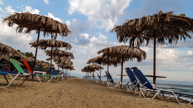 Отдых на берегу моря шезлонги и соломенные зонтики на пляже греция остров тасос