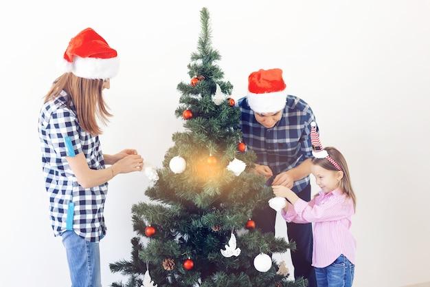 휴일, 부모 및 축하 개념 - 흰색 배경에 있는 거실에 싸구려로 크리스마스 트리를 장식하는 행복한 가족.