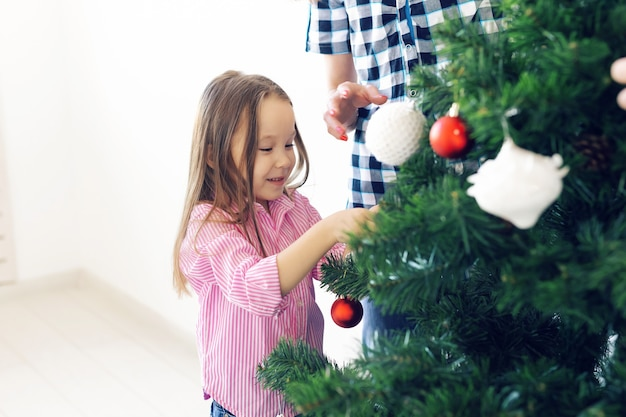 Holidays, parents and celebrating concept - happy family decorating a christmas tree with baubles in the living-room on white background.