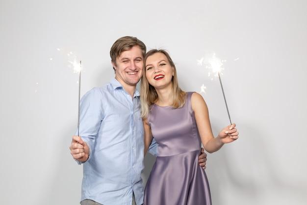 休日、パーティー、お祝いのコンセプト-白い壁に線香花火を持つ若いカップル。