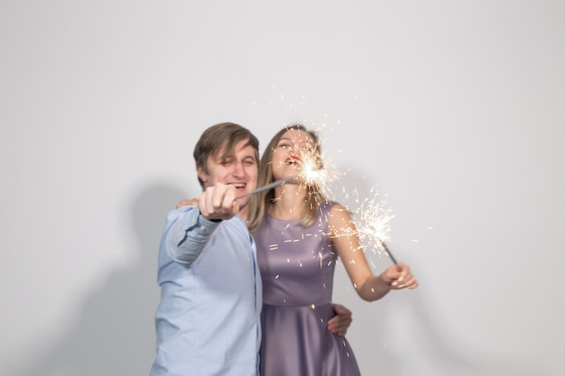 휴일, 파티 및 축하 개념 - 흰색 바탕에 폭죽이 있는 젊고 재미있는 행복한 커플.