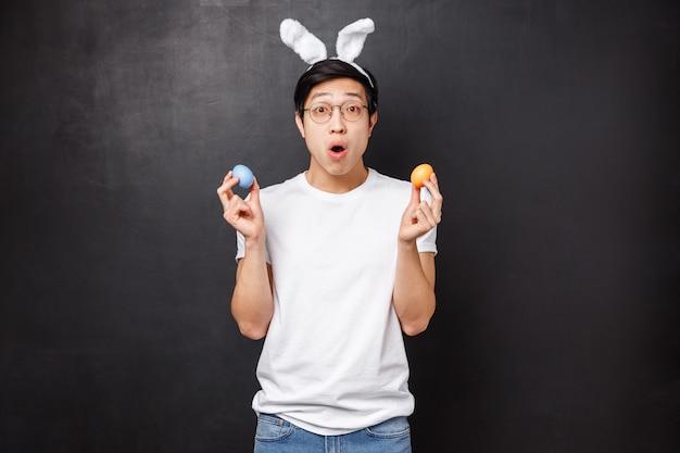Праздники, вечеринки и концепция пасхи. удивленный молодой азиатский парень в кроличьих ушах держит крашеные яйца, изучая традиции подружки, с открытым ртом очаровывает знакомство с новой культурой,