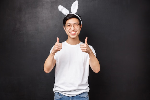 Праздники, вечеринки и концепция пасхи. портрет симпатичного и забавного азиатского молодого парня в ушах кролика порекомендует что-то, даст хороший совет, гарантирует качественное шоу, показывает палец вверх и улыбается счастливо Premium Фотографии