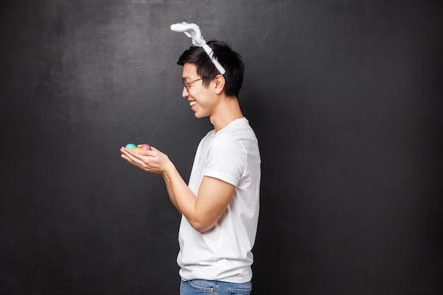 Праздники, вечеринки и концепция пасхи. профиль портрет веселого милого молодого азиатского человека в ушах кролика и белой футболке, стоя с крашеными яйцами в руках