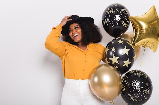 휴일, 파티 및 재미 개념. 화이트 파티 풍선과 함께 웃는 젊은 아프리카 계 미국인 젊은 여자의 초상화