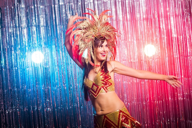 Holidays, party, dance and nightlife concept - beautiful woman dressed for carnival night.
