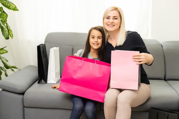 休日、プレゼント、クリスマス、クリスマス、誕生日のコンセプト-ギフトバッグを持つ幸せな母と子の女の子
